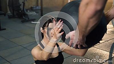 Belle femme de sport pr?parant l'ABS s'exercer avec la boule d'a?robic avec l'entra?neur masculin banque de vidéos