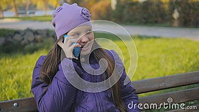 Belle fille de l'adolescence souriant et parlant au téléphone en parc d'automne Supports dentaires Au ralenti clips vidéos