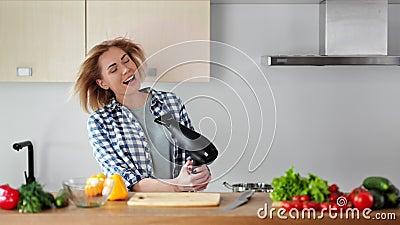 Belle jeune chanson de chant de femme au foyer et danse pendant les cheveux de séchage avec le dessiccateur de coup à la cuisine clips vidéos