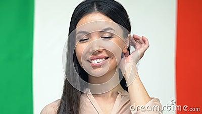 Belle jeune femme, caméra souriante sur fond de drapeau italien, culture banque de vidéos