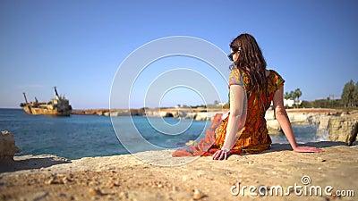 Belle jeune femme dans une robe se reposant par le rivage rocheux sur le fond de la vue pittoresque d'un vieux bateau, ciel et banque de vidéos