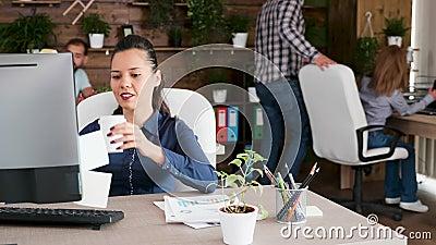 Belle jeune femme entrepreneur tapant et prenant son café au bureau banque de vidéos
