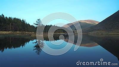 Belle longueur de lac immobile et montagnes contre le ciel clips vidéos