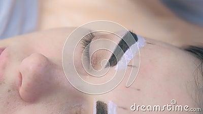 Bellezza che sputa sopracciglia con pinzette per donna nel salone di bellezza archivi video