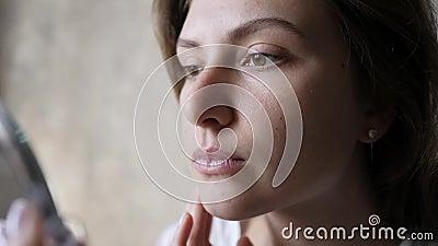 Bellezza, trucco, occultatore La giovane bella donna applica il trucco di base e guarda il riflesso in uno specchio a mano archivi video