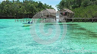 Bellissima laguna blu con alcune capanne di bambù, kordiris homestay, palma di fronte, Gam Island, West Papuan, Raja Ampat archivi video
