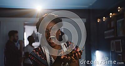 Bellissima ragazza africana allegra che ride, che sputa coriandoli per il divertimento durante le celebrazioni atmosferiche al ra video d archivio