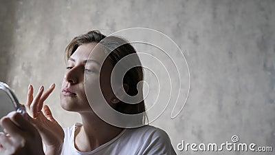 Bellissime tracce di beige nascondono il volto di una donna, le zigomi e le guance La ragazza carina applica il trucco di base a  video d archivio