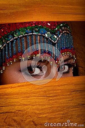 Belly dancer peeking from behind veil