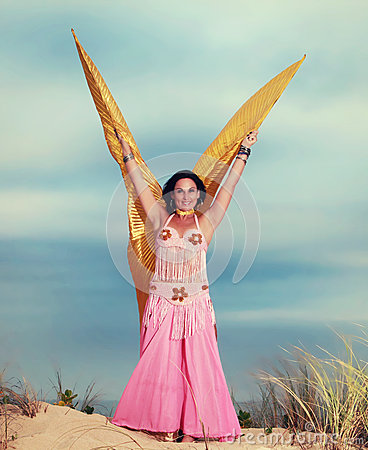 Belly dancer with wings performing on the beach