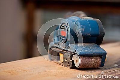 Belt sander on a wooden surface