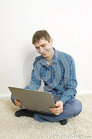 Bemannen Sie das Sitzen auf dem Boden unter Verwendung eines Laptops