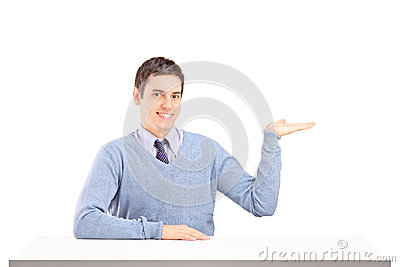 Bemannen Sie das Sitzen auf einer Tabelle und das Gestikulieren mit seiner Hand