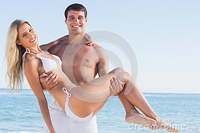 Bemannen Sie das Tragen seiner hübschen Freundin, die an der Kamera lächelt