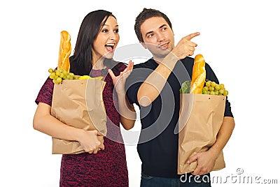 Bemannen Sie das Zeigen auf seine überraschte Frau auf das Einkaufen