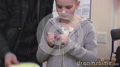 Bemannen Sie helfendes kleines Mädchen mit Blume auf dem Kopf, der durch Häkelarbeit strickt festival kreation handmade stock video