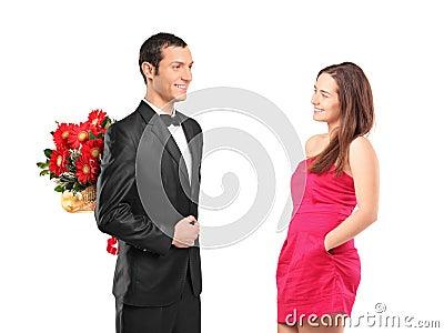 Bemannen Sie versteckenden Blumenstrauß der Blumen von einer Frau