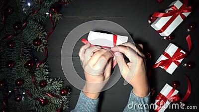 Bemannt Hände einwickeln ein Geschenk Schwarzer Hintergrund von Weihnachten schmückte mit Flitter und Lichtern stock video