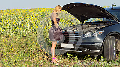 Bemused woman looking at car engine
