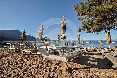 Bench tables with umbrellas by lake on sand