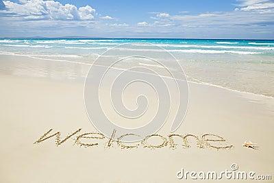 Benvenuto scritto su una spiaggia