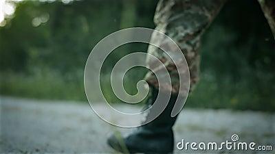 Bepaalde militaire mens die over zandige weg lopen stock video