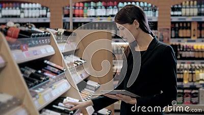 Berater in der Weinhandlung, Oman im Speicher, der den Wein übereinstimmt Check-Liste oder Informationen im Tablet-Computer wählt stock video