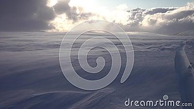Bergsnäckdrift i svenska Lappland Sun lyser genom tunga moln Höghastighetsförhållanden vid snödrift Gammalt snömobilspår stock video