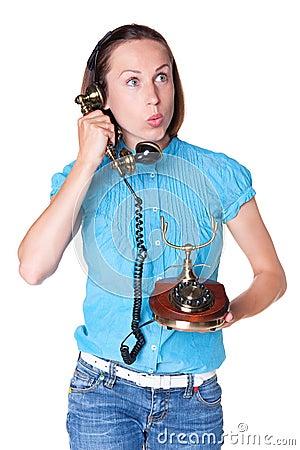 Überraschte Frau, die im Retro- Telefon spricht