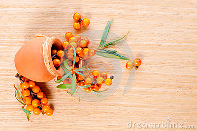 Berries are scattered out of a ceramic pot on a wooden backgroun Stock Photo