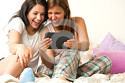 Best friends laughing browsing social network
