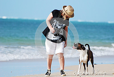 Best friends-Woman & pet dog walking on beach
