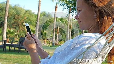 Betere vrouw die in de zomer smartphone in de tuin gebruikt stock video