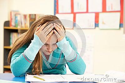 Betontes Schulmädchen, das im Klassenzimmer studiert