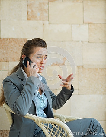 Betrokken bedrijfsvrouw die mobiele telefoon spreekt