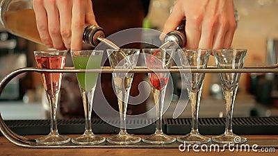 Bevanda di Pouring Colorful Alcoholic del barista nei vetri di colpo closeup stock footage