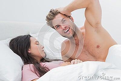 Bez koszuli mężczyzna pozuje obok jego sypialnego partnera