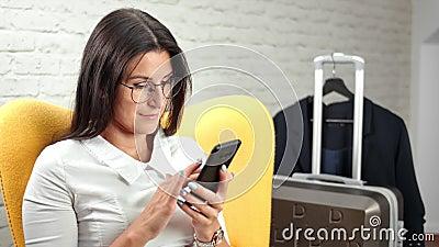 Bezig met een goede, stijlvolle jonge zakenvrouw die tijdens een zakenreis met een smartphone chatten stock video