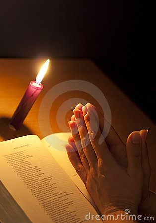 Bible candle and praying hands