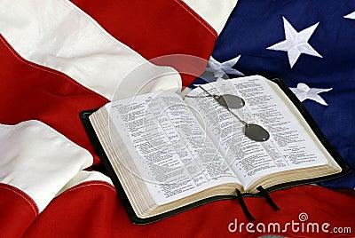Biblia con las etiquetas de perro en indicador de los E.E.U.U.