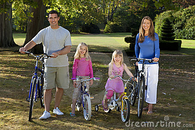 Bicicletas felizes da equitação da família em um parque