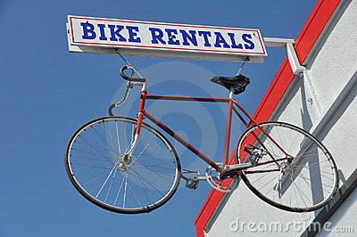 Bicycle hanges from a Bike Rentals sign outside