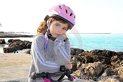 Bicycle little pensive girl in rocky beach