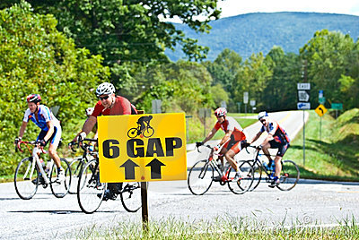 Bicycle Riders Behind Sign Editorial Photo