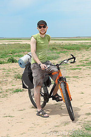 Bicycle tourist standing on road and smiling