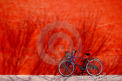 Bicycle under red wall