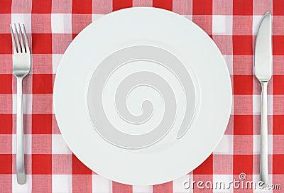 Bielu talerz na czerwonym i białym w kratkę płótnie