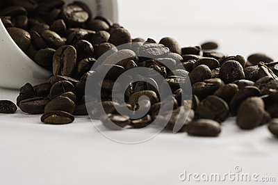 BIG COFFEE BEANS with with white cup closeup