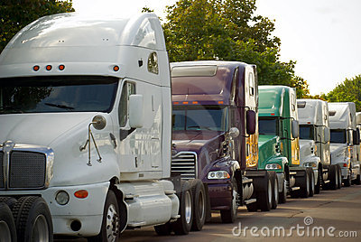 Big commercial transportation trucks lined on road