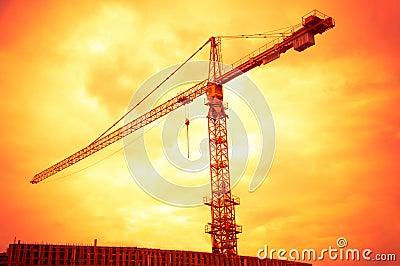 Big crane on sunset orange sky background
